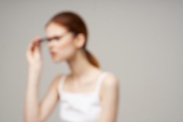 Kobieta w białych okularach tshirt w rękach jasnego tła astygmatyzmu