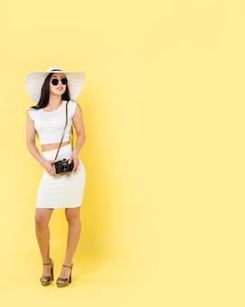 Kobieta w białych strojach i kapeluszu pozyci i mienia kamerze