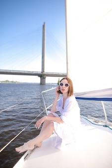 Kobieta w białych strojach pozuje siedzieć na jachcie na tle rzeki i mostu