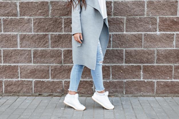 Kobieta w białych trampkach i dżinsach, szary płaszcz w pobliżu ściany z cegły