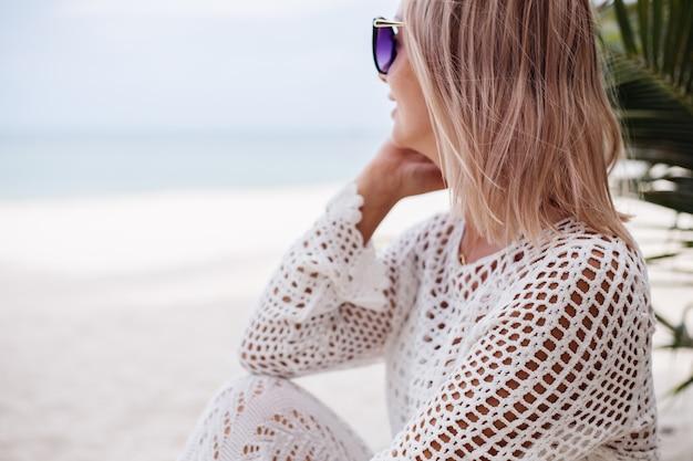 Kobieta w białych ubraniach z dzianiny na plaży