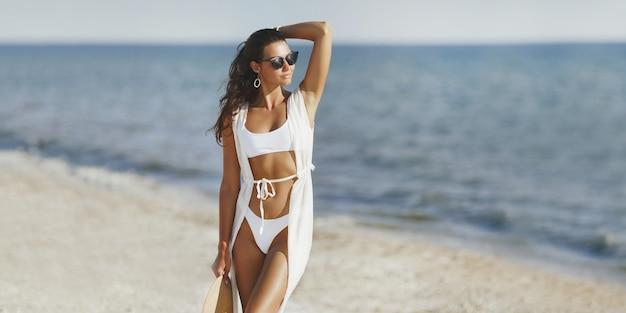 Kobieta w białym bikini i okularach przeciwsłonecznych pozuje na plaży