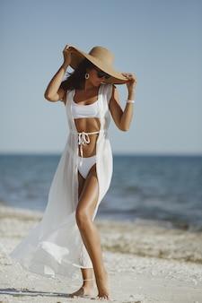 Kobieta w białym bikini, kapeluszu i okularach przeciwsłonecznych pozuje na plaży