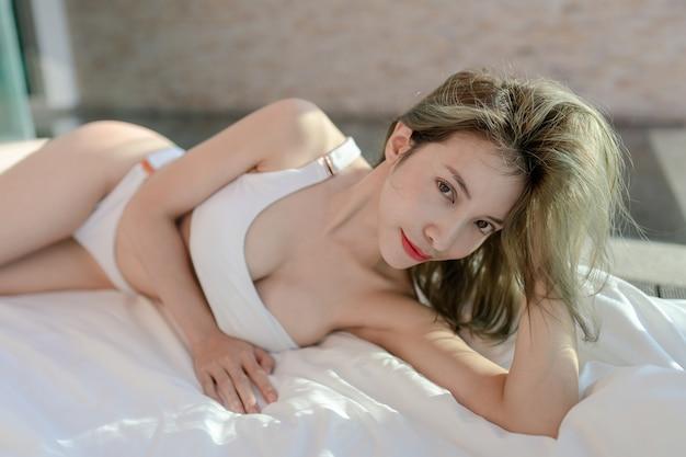 Kobieta w białym bikini, leżąc na białej pościeli.