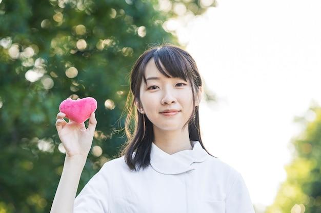Kobieta w białym fartuchu z dodatkiem w kształcie serca