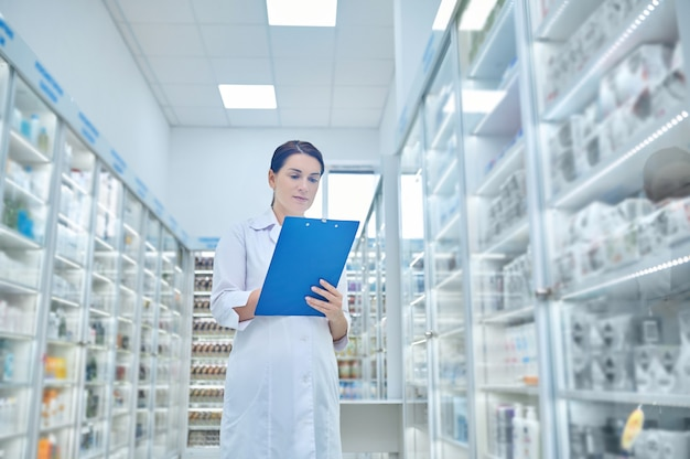 Kobieta w białym fartuchu z folderem w aptece