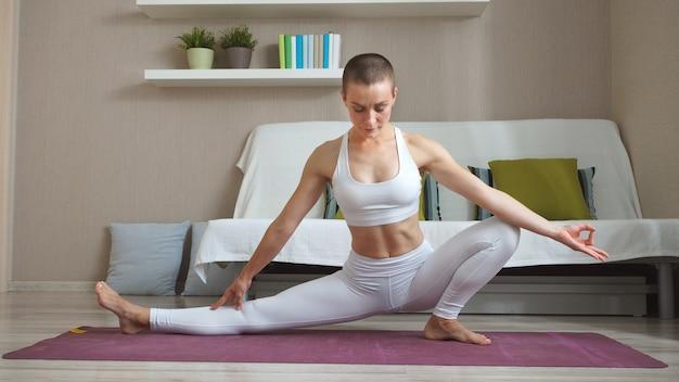 Kobieta w białym garniturze fitness robi joga siedząc w salonie. samoizolacja i sport w domu