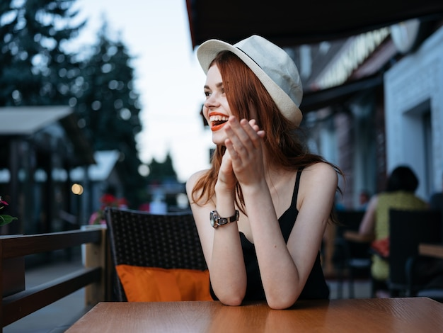 Kobieta w białym kapeluszu i czarnej sukni przy stoliku w kawiarni na ulicy