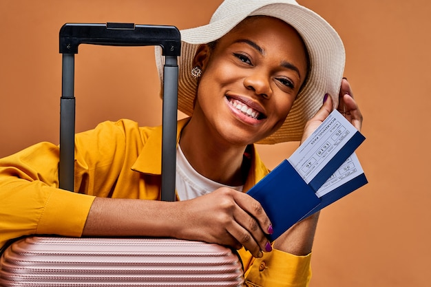 Kobieta w białym kapeluszu i żółtej kurtce, oparta na walizce, trzyma w ręku niebieski paszport z dwoma biletami. koncepcja podróży