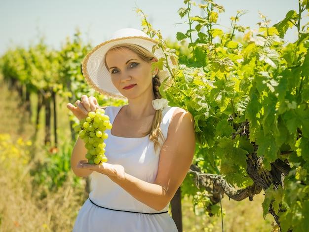 Kobieta w białym kapeluszu pokazuje kiść dojrzałych zielonych winogron.