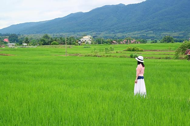 Kobieta w białym kapeluszu spacer po żywych zielonych polach ryżowych
