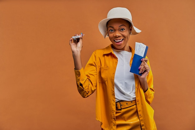 Kobieta w białym kapeluszu w żółtej koszuli uśmiecha się do kamery z samolocikiem z paszportem z biletami w ręce. koncepcja podróży