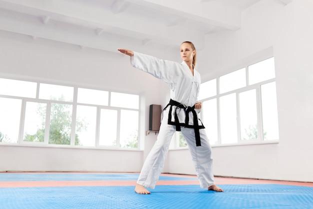 Kobieta w białym kimonie z czarnym pasem treningowym karate.