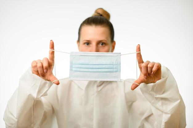 Kobieta w białym kombinezonie ochronnym trzyma maskę przed jej twarzą