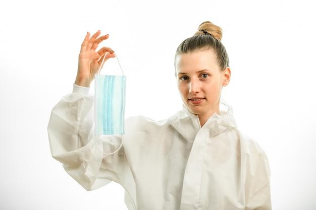 Kobieta w białym kombinezonie ochronnym trzyma w ręku maskę chirurgiczną