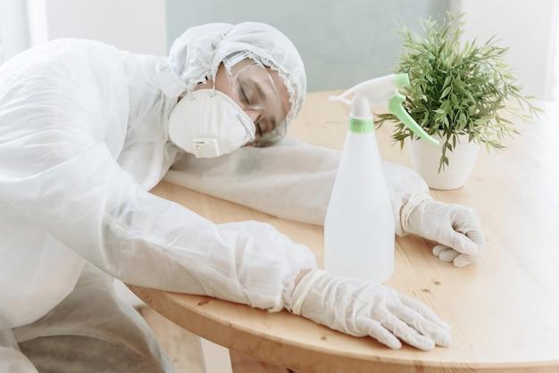 Kobieta w białym kombinezonie, rękawiczkach i respiratorze odpoczywa lub śpi przy stole