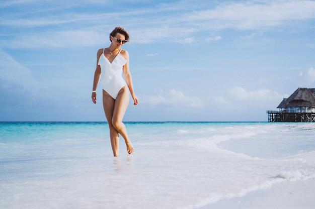 Kobieta w białym kostiumie kąpielowym nad oceanem
