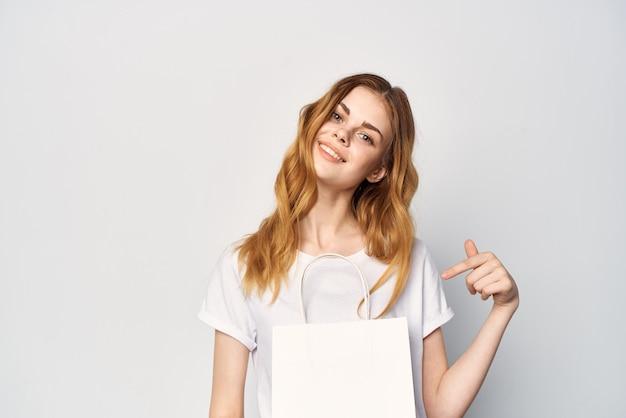 Kobieta w białym opakowaniu tshirt w rękach prezent na zakupy w tle światła