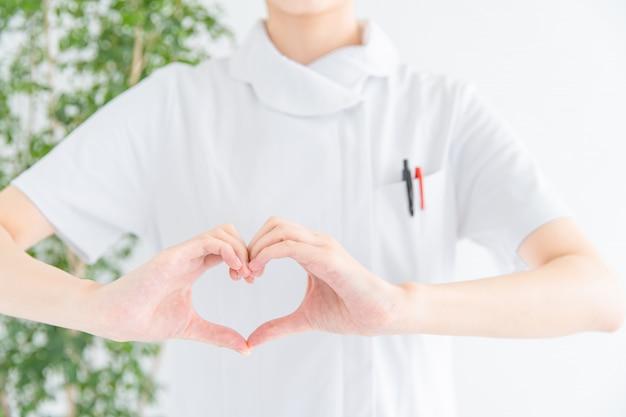 Kobieta w białym płaszczu co serce z rąk