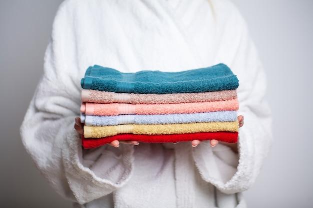 Kobieta w białym płaszczu gospodarstwa stos kolorowych ręczników