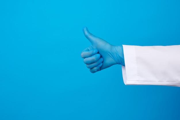 Kobieta w białym płaszczu, ubrana w niebieskie lateksowe rękawiczki medyczne na rękach, pokazująca jak