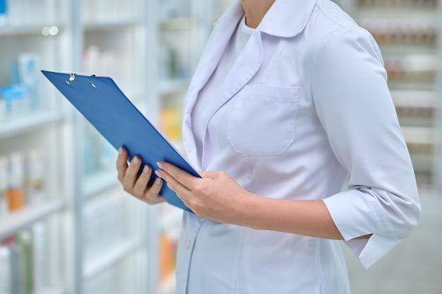 Kobieta w białym płaszczu z niebieską teczką