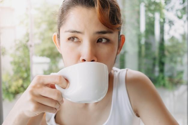 Kobieta w białym podkoszulku pije gorący napój w filiżance