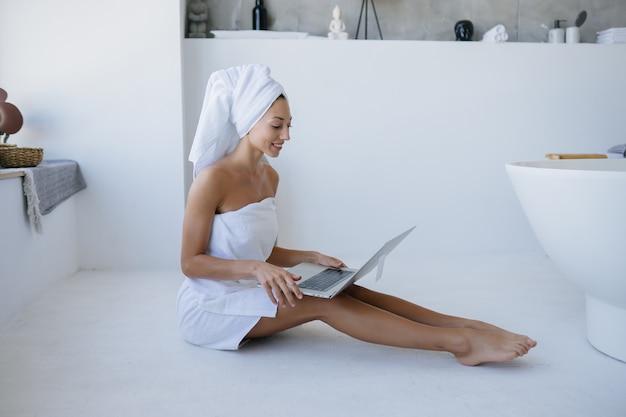 Kobieta w białym ręczniku siedzi w łazience i korzysta z laptopa.