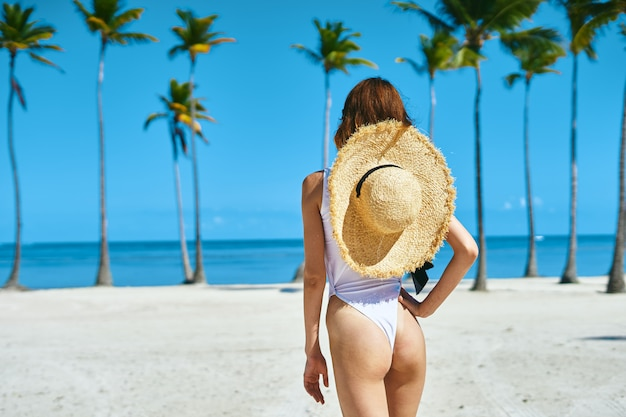 Kobieta w białym stroju kąpielowym na plaży