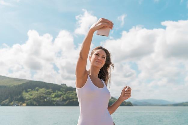 Kobieta w białym stroju kąpielowym robi selfie telefonem na plaży