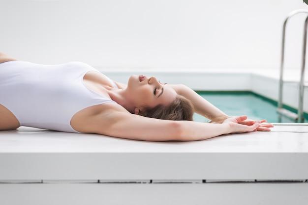 Kobieta w białym stroju kąpielowym w pobliżu basenu