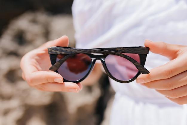 Kobieta w białym stroju trzymając ciemne okulary. zdjęcie kobiecych rąk z okularami przeciwsłonecznymi.