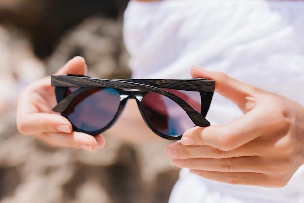 Kobieta w białym stroju trzymając okulary. zdjęcie europejskiej kobiety stojącej na zewnątrz w ciemnych okularach przeciwsłonecznych.