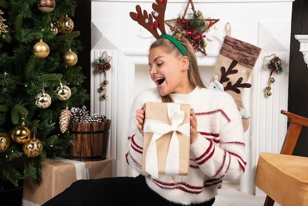Kobieta w białym swetrze szczęśliwie pokazując obecny w świątecznym wystroju wnętrz.