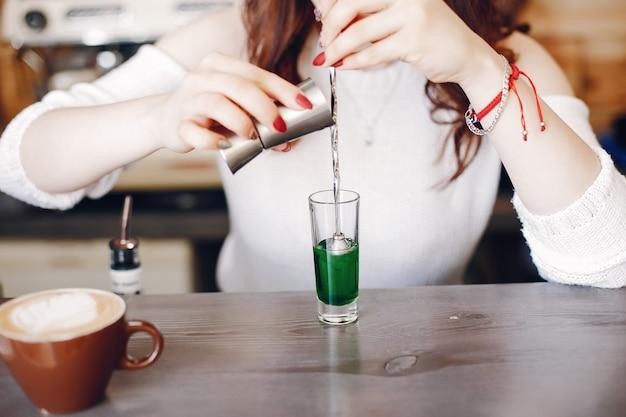 Kobieta w białym swetrze, wlewając zielony syrop do szkła
