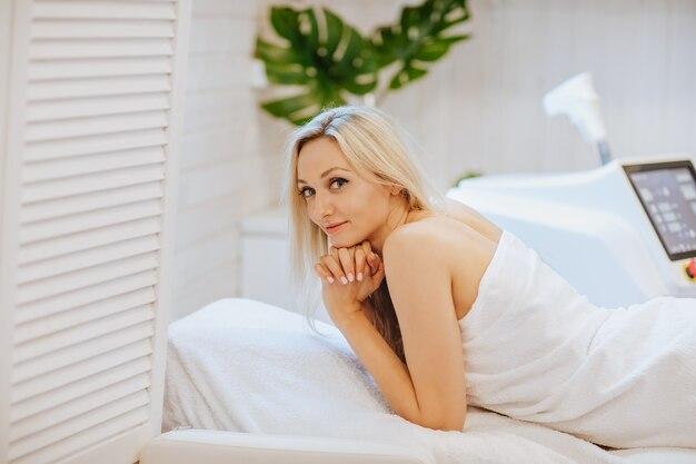 Kobieta w białym szlafroku r. na krześle kosmetologii