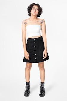 Kobieta w białym topie bandeau i czarnej spódnicy w kształcie litery a z pełnym designem przestrzenią na całym ciele