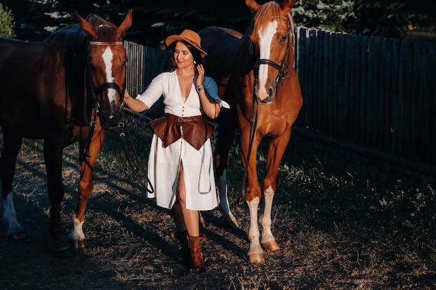 Kobieta w białym ubraniu i kapeluszu spaceruje z końmi na łonie natury