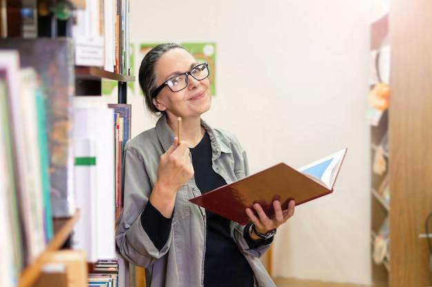 Kobieta w bibliotece pracuje przy biurku. kobieta w średnim wieku ze stosami książek. ona studiuje.