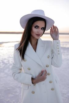 Kobieta w bieli kobiety w zimowych butach europejka w płaszczu uśmiechnięta w zimny dzień wesoła jasnowłosa kobieta bawiąca się zimą sesja zdjęciowa zimą jezioro nad śniegiem ciepłe buty