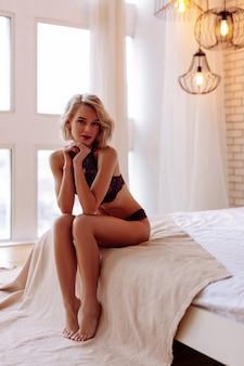 Kobieta w bieliźnie. szczupła młoda kobieta z bobem w seksownej bieliźnie siedzi na łóżku underwear