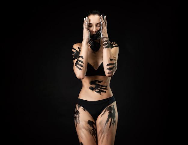 Kobieta w bieliźnie umazana czarną farbą na czarnym tle