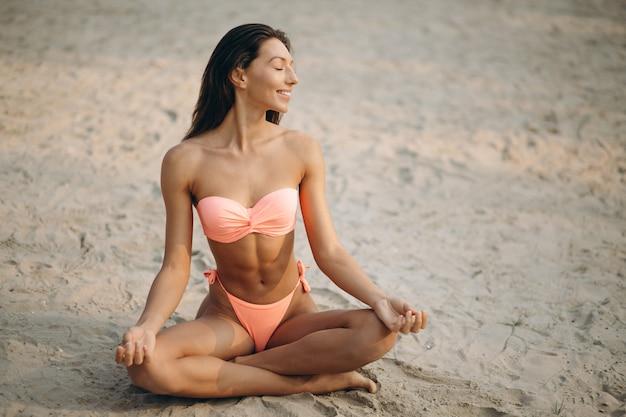 Kobieta w bikini ćwiczy joga przy plażą
