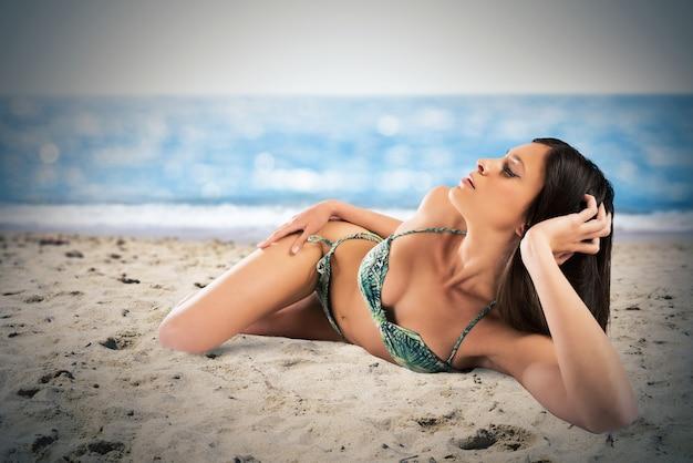 Kobieta w bikini, leżąc na linii brzegowej