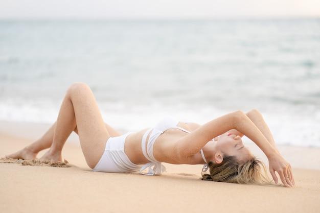 Kobieta w bikini, leżąc na piaszczystej plaży relaksujące opalanie.