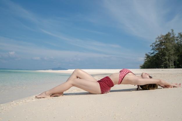 Kobieta w bikini leżąc na wodzie morskiej przy białej, piaszczystej plaży. błękitny krajobraz morza i nieba. letni wypoczynek.