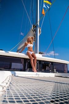 Kobieta w bikini opalająca się i relaksująca na letnim rejsie katamaranem