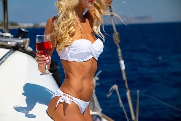 Kobieta w bikini opalająca się i relaksująca pijąca wino podczas letniego rejsu katamaranem