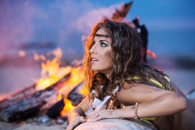 Kobieta w bikini pozuje blisko ogniska