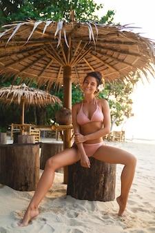 Kobieta w bikini siedzi w barze na plaży